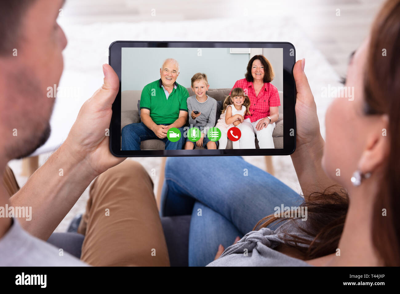 Couple Sitting On Sofa Video Conferencing With Their Happy Family Using Digital Tablet - Stock Image