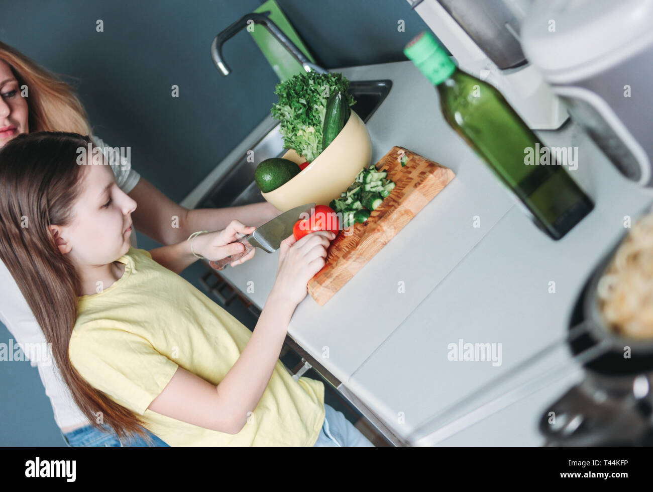 Tween girl and her mother making vegetable salad in the kitchen at home - Stock Image