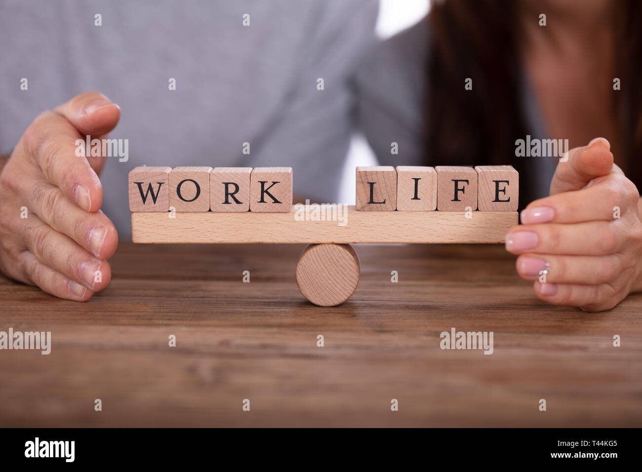 Close-up Of Couple's Hand Protecting Work And Life Wooden Blocks Balancing On Seesaw - Stock Image