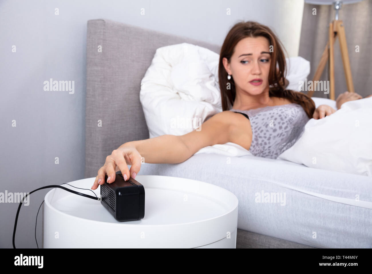 Young Woman In Bed Reaching For Snooze Button In Bedroom - Stock Image