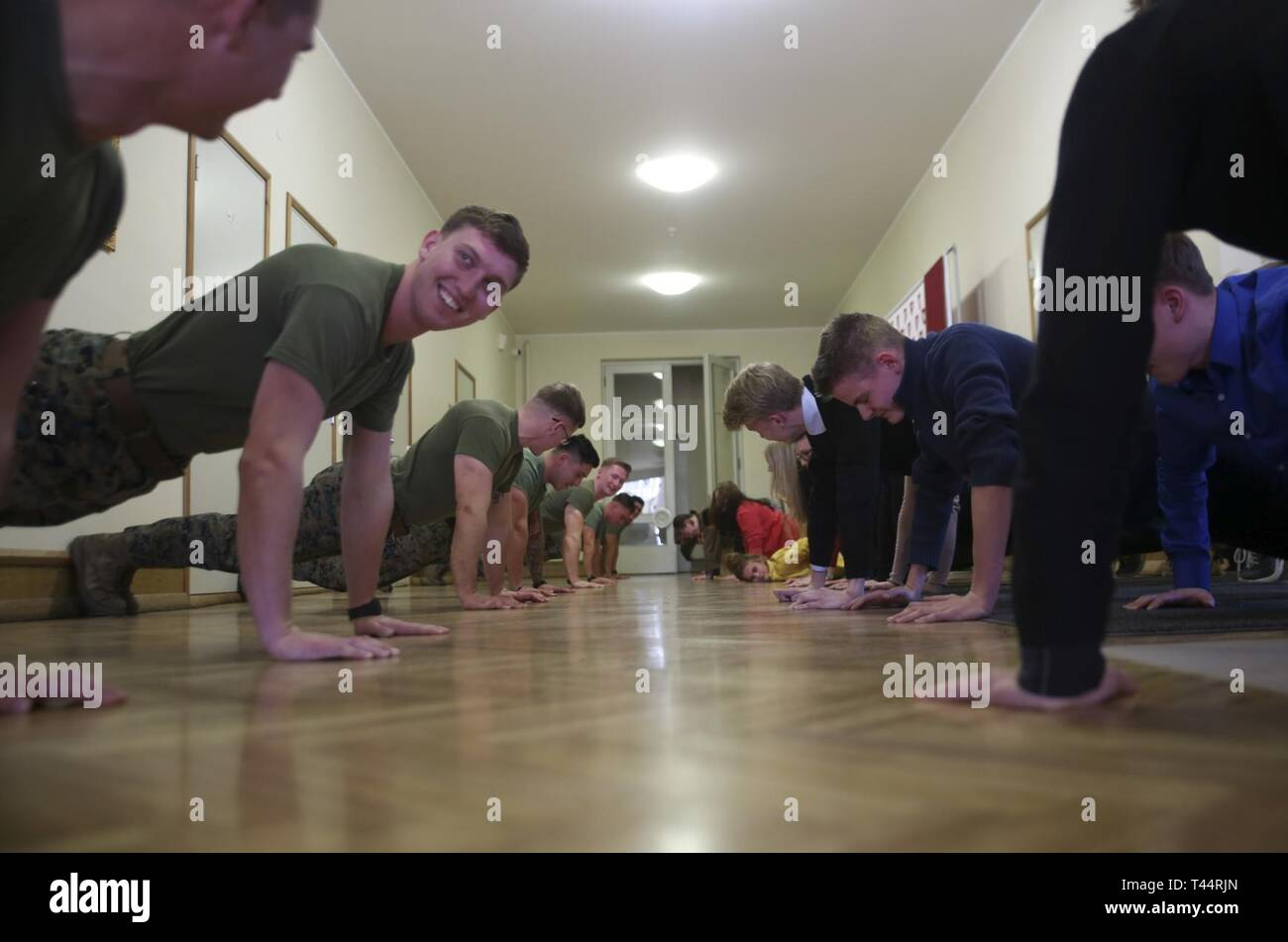U.S. Marines with Fleet Anti-terrorism Security Team-Europe lead high school students in an exercise routine to demonstrate the importance of health and fitness at at Jakob Westholmi Gymnasium, Tallinn, Estonia, Feb. 21, 2019. Following Exercise Winter Camp 19, FAST-EUR Marines spent the week traveling across the country to meet with members of the local community in a series of civil-military outreach engagements designed to build shared understanding, promote our strong bilateral relationship, and celebrate 101 years of Estonian independence. (Marine Corps Europe and Africa Stock Photo