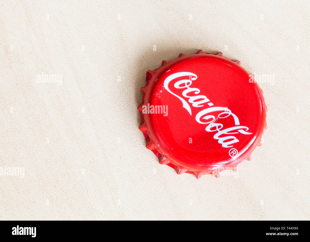 MOSCOW, RUSSIA - APRIL 4, 2019: used crown cork bottle cap from Coca-Cola beverage on wooden board with copyspace. Coca-Cola (Coke) is carbonated soft - Stock Image