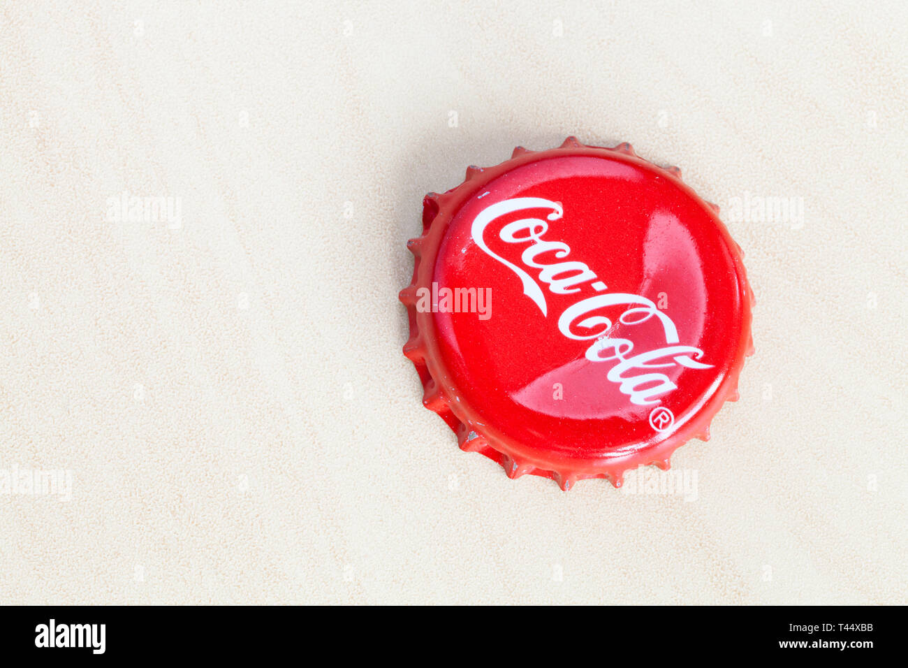 MOSCOW, RUSSIA - APRIL 4, 2019: old crown cork bottle cap from Coca-Cola beverage on wooden board with copyspace. Coca-Cola (Coke) is carbonated soft  - Stock Image