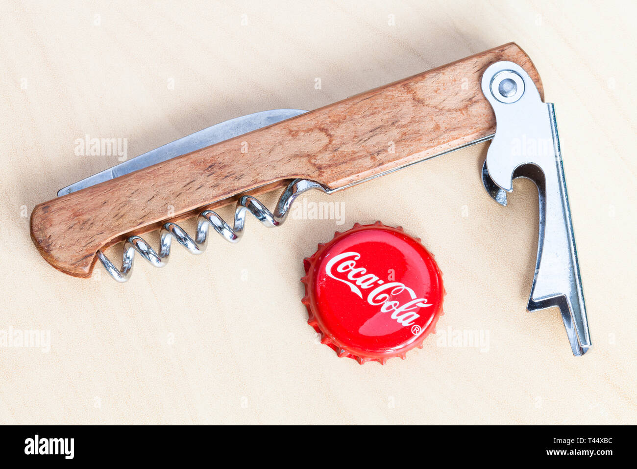MOSCOW, RUSSIA - APRIL 4, 2019: used crown cork bottle cap from Coca-Cola beverage and bottle opener on wooden board. Coca-Cola (Coke) is carbonated s - Stock Image