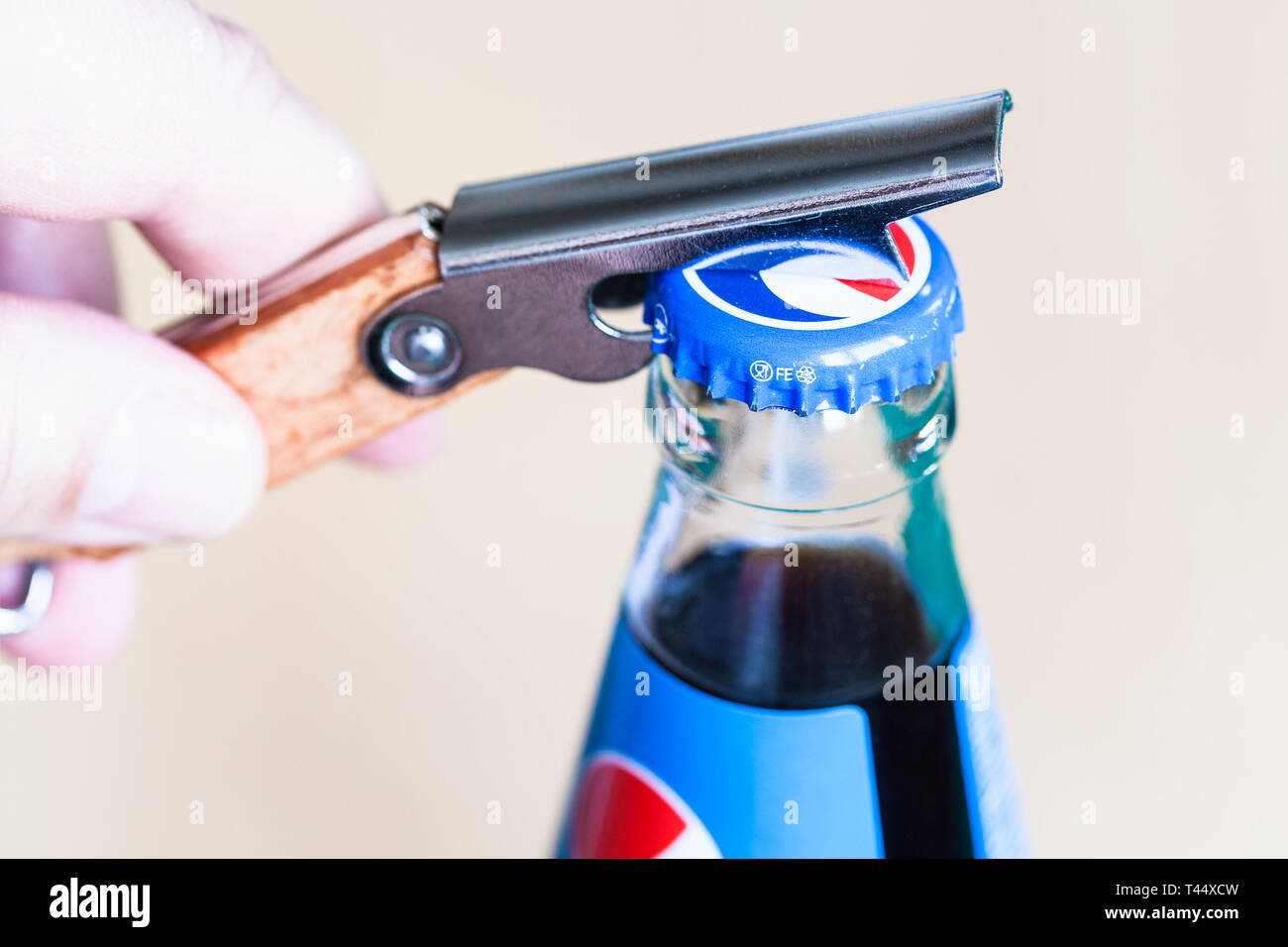 MOSCOW, RUSSIA - APRIL 4, 2019: opening a cap of Pepsi glass bottle