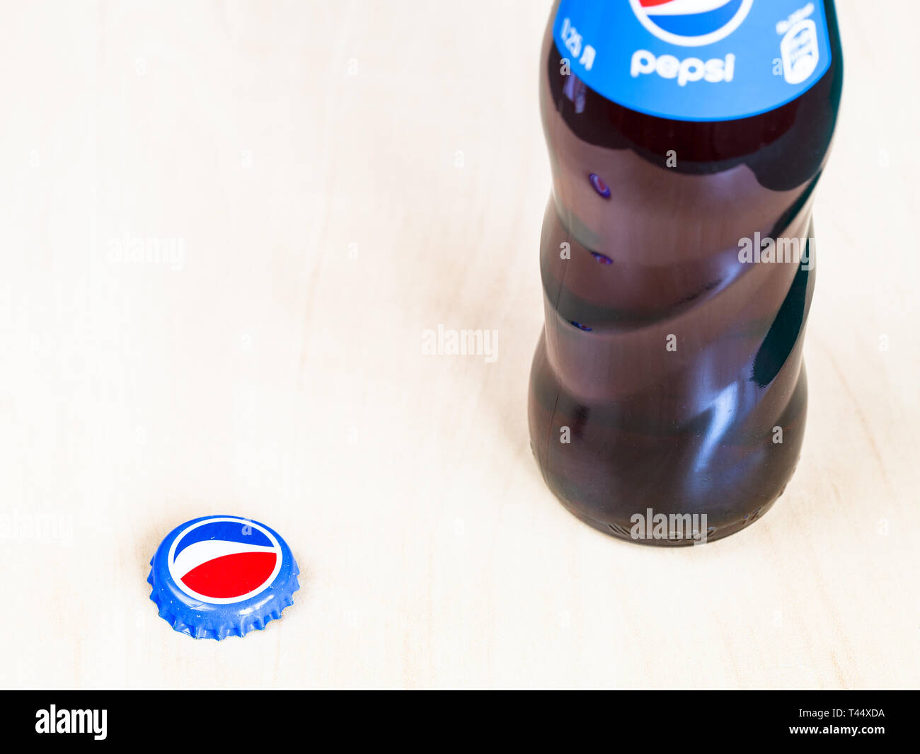 MOSCOW, RUSSIA - APRIL 4, 2019: glass bottle and used crown cork bottle cap from Pepsi beverage on wooden board. Pepsi is carbonated soft drink manufa - Stock Image