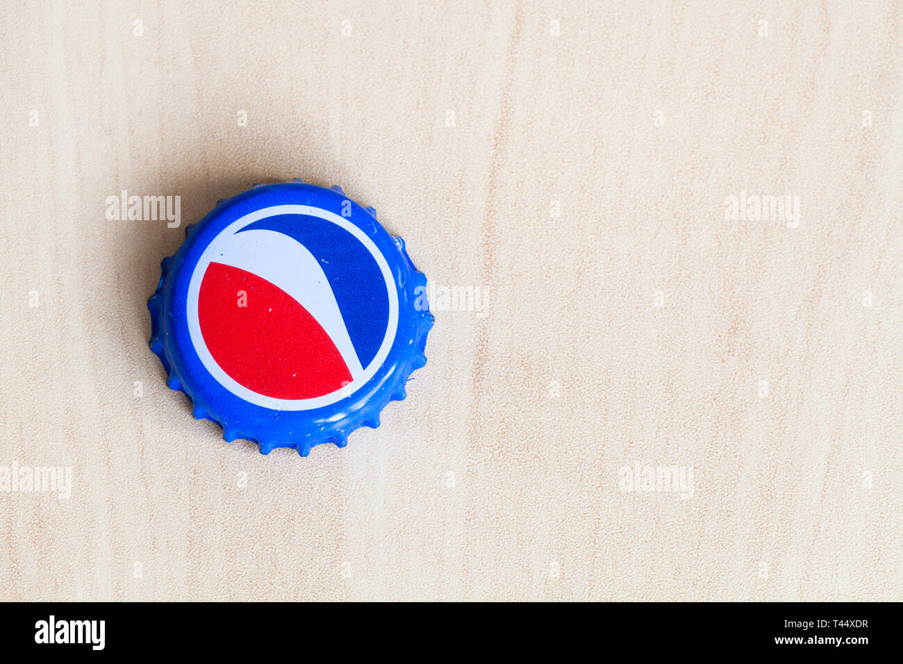 MOSCOW, RUSSIA - APRIL 4, 2019: used crown cork bottle cap from Pepsi beverage on wooden board with copyspace. Pepsi is carbonated soft drink manufact - Stock Image