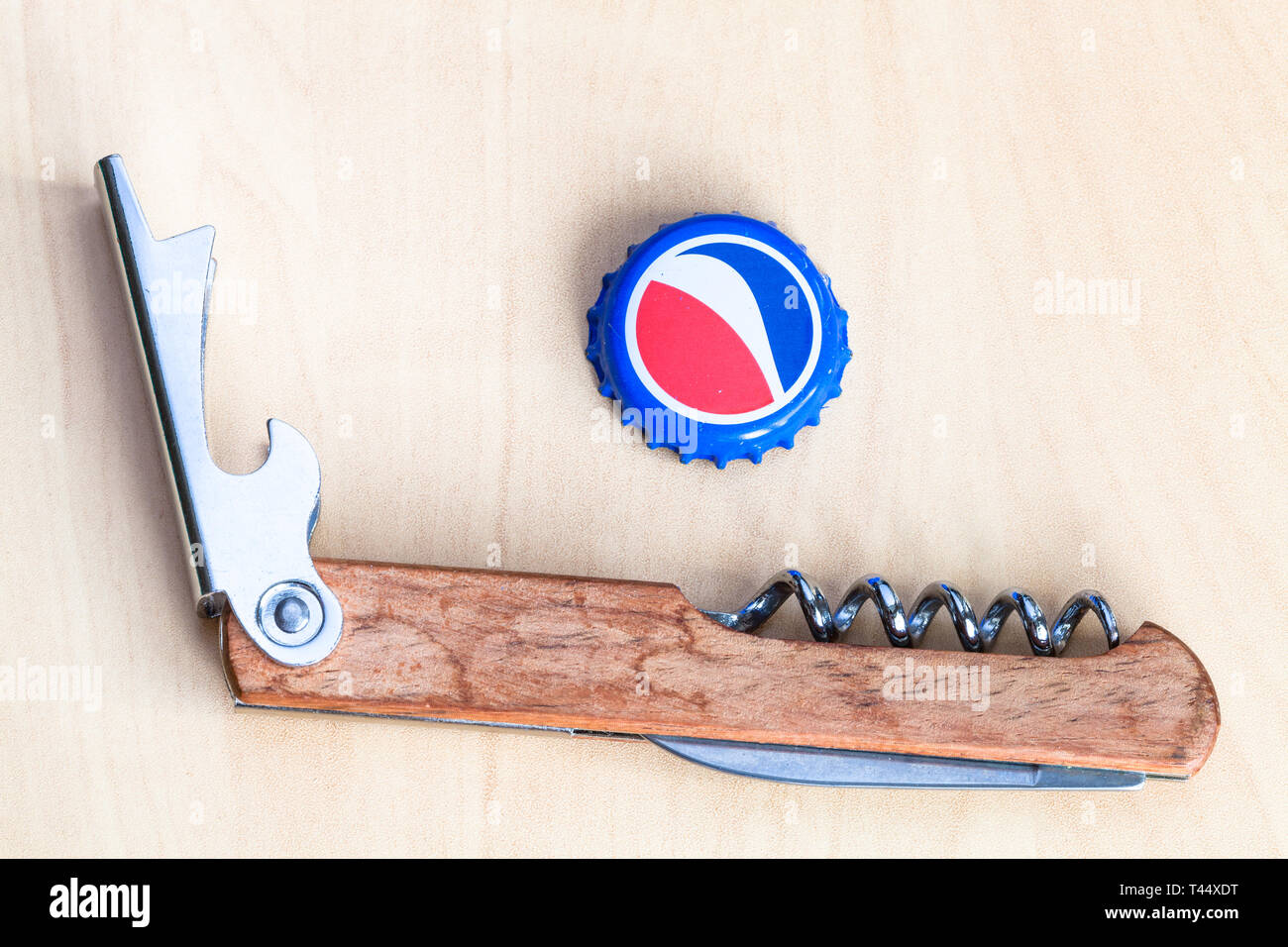 MOSCOW, RUSSIA - APRIL 4, 2019: used crown cork bottle cap from Pepsi beverage and bottle opener on wooden board. Pepsi is carbonated soft drink manuf - Stock Image
