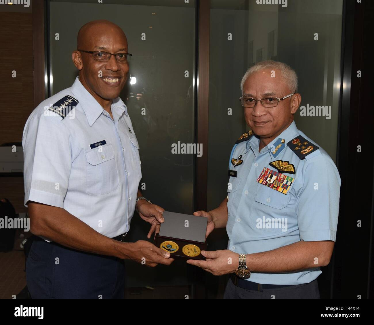 U.S. Air Force Gen. CQ Brown, Jr., Pacific Air Forces commander, left, presents a coin to Gen. Tan Sri Dato' Sri Hj Affendi bin Buang, Royal Malaysian Air Force chief, following a bilateral meeting in Melbourne, Victoria, Australia, Feb. 24, 2019. The two leaders met ahead of the 2019 Australian International Aerospace & Defence Exposition and Airshow Stock Photo