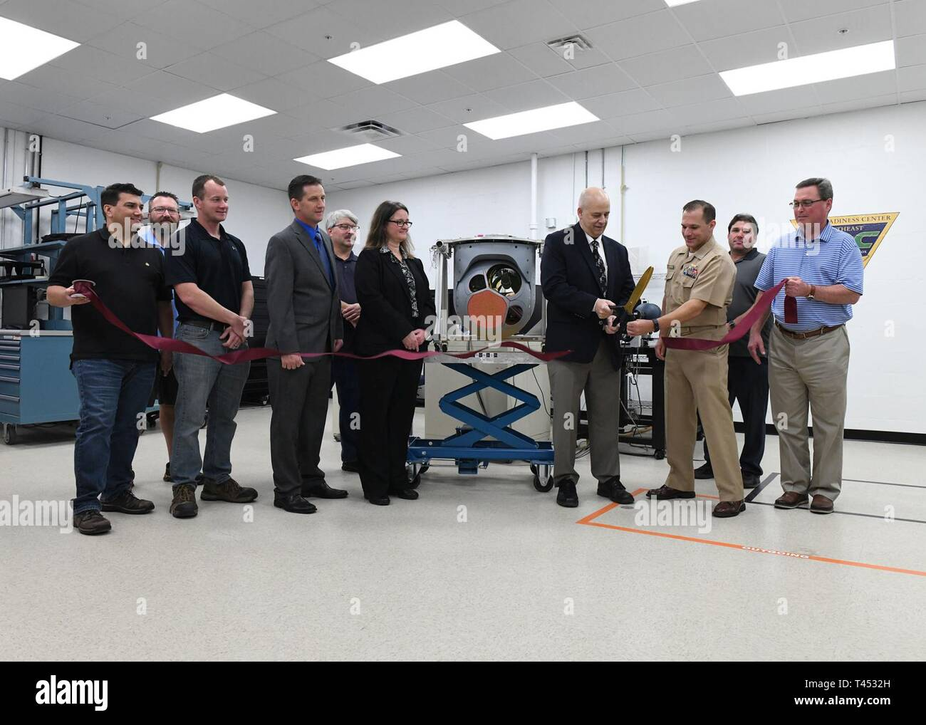 JACKSONVILLE, Fla. (Feb. 27, 2019) Members of Fleet Readiness Center Southeast and L3 WESCAM cut the ribbon to declare the Navy depot's maintenance capability on the company's MX-20 turret on Wednesday. - Stock Image