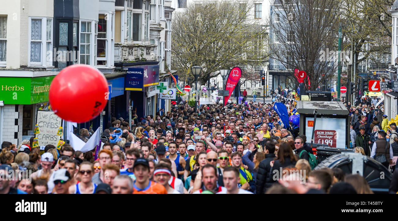 Brighton, Sussex, UK. 14th Apr, 2019. Thousands of runners and spectators in the narrow St James's Street area of Brighton take part in this years Brighton Marathon which is celebrating its 10th anniversary Credit: Simon Dack/Alamy Live News - Stock Image
