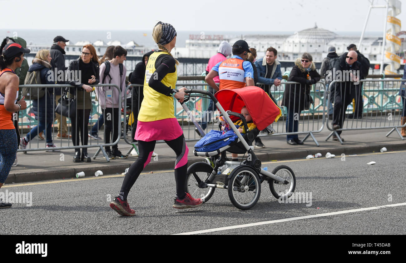 Brighton UK 14th April 2019 -   A woman with a baby in a pram takes part in this years Brighton Marathon which is celebrating its 10th anniversary Credit: Simon Dack/Alamy Live News Stock Photo