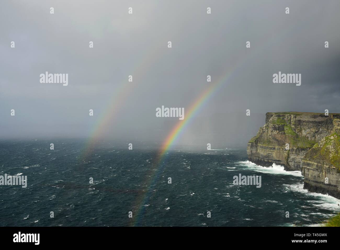 A double rainbow over the Cliffs of Moher on the west coast of Ireland in County Clare. - Stock Image