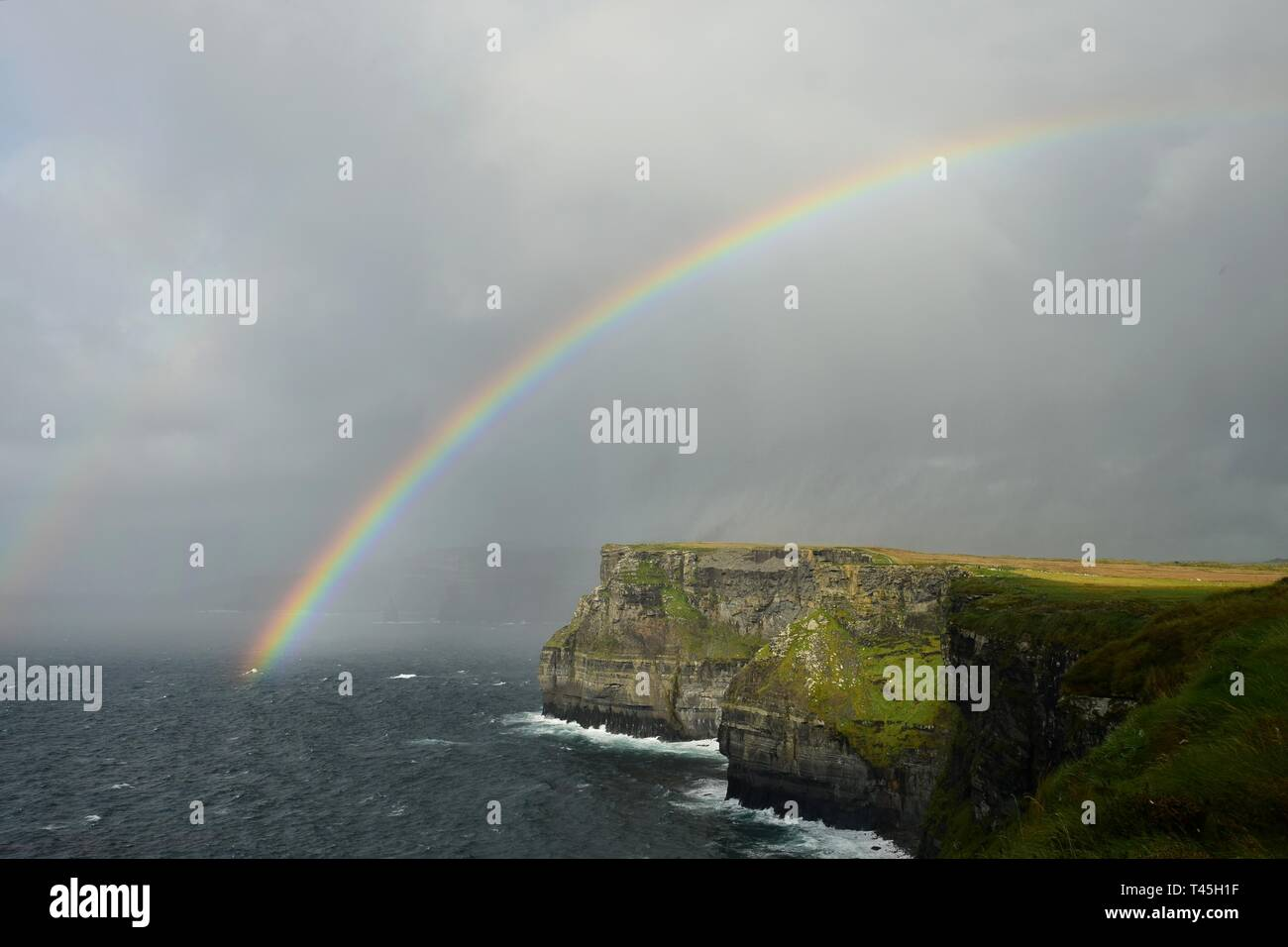 A rainbow over the Cliffs of Moher on the west coast of Ireland in County Clare. - Stock Image
