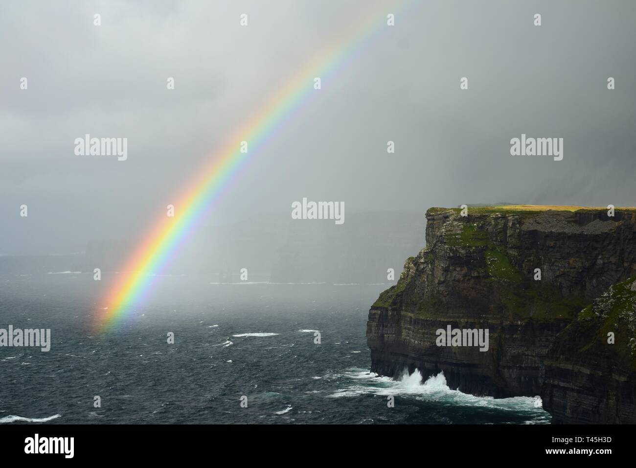 A colorful rainbow over the Cliffs of Moher on the west coast of Ireland in County Clare. - Stock Image