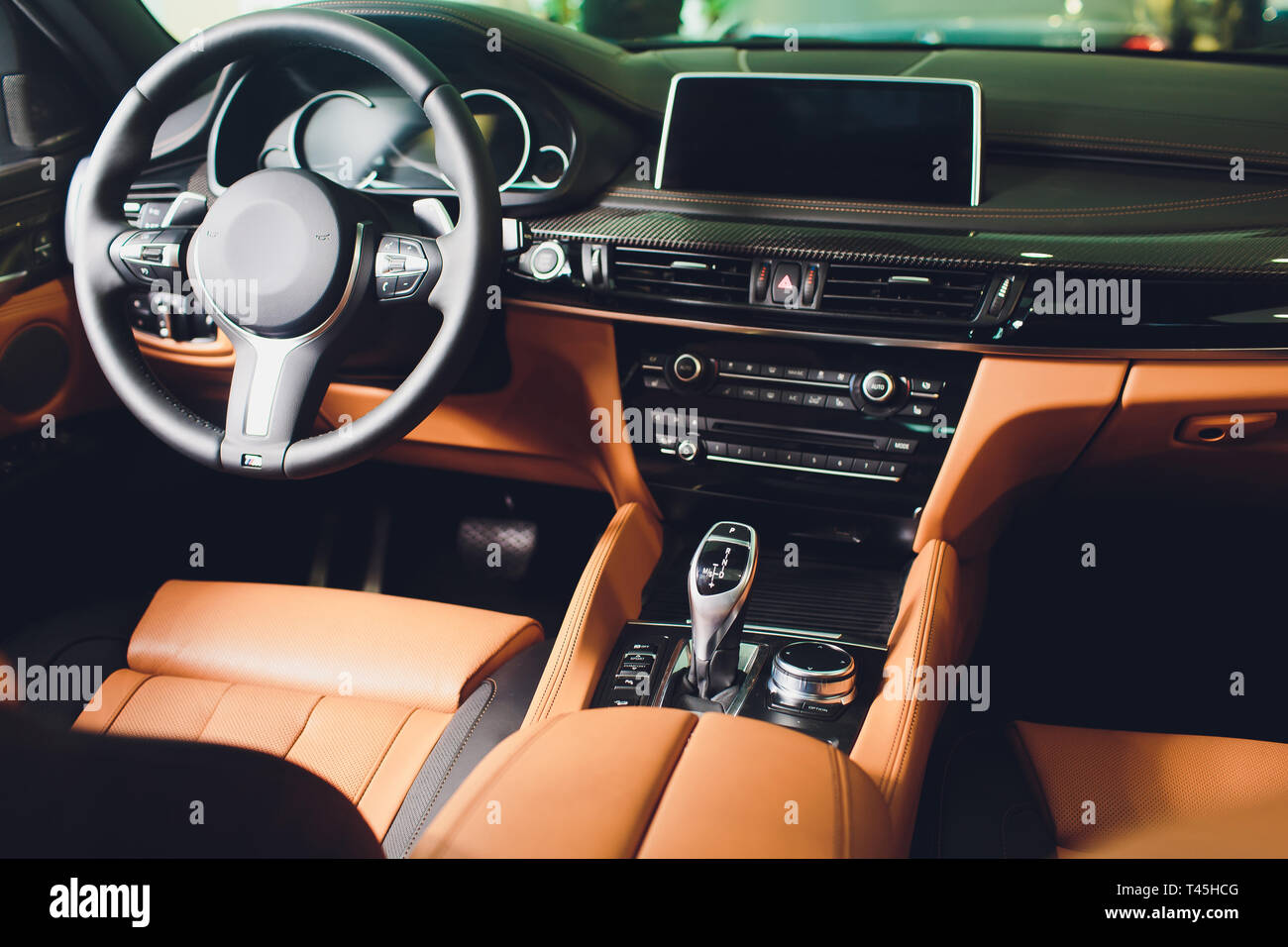 Modern Luxury car inside. Interior of prestige modern car. Comfortable leather brown seats. Orange perforated leather cockpit. - Stock Image