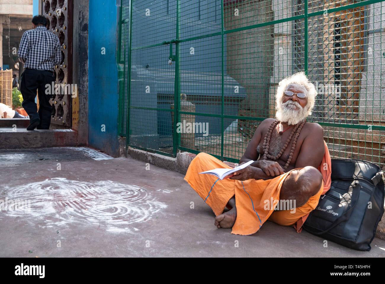 Horizontal portrait of an old Sadhu sitting at the gates of the Kapaleeshwarar Temple in Chennai, India. - Stock Image