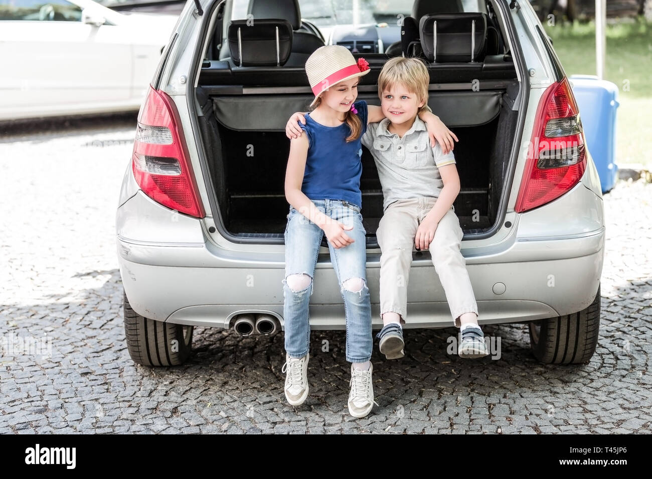 little sister and brother sitting in the trunk of a car with suitcases. the concept of family travel - Stock Image