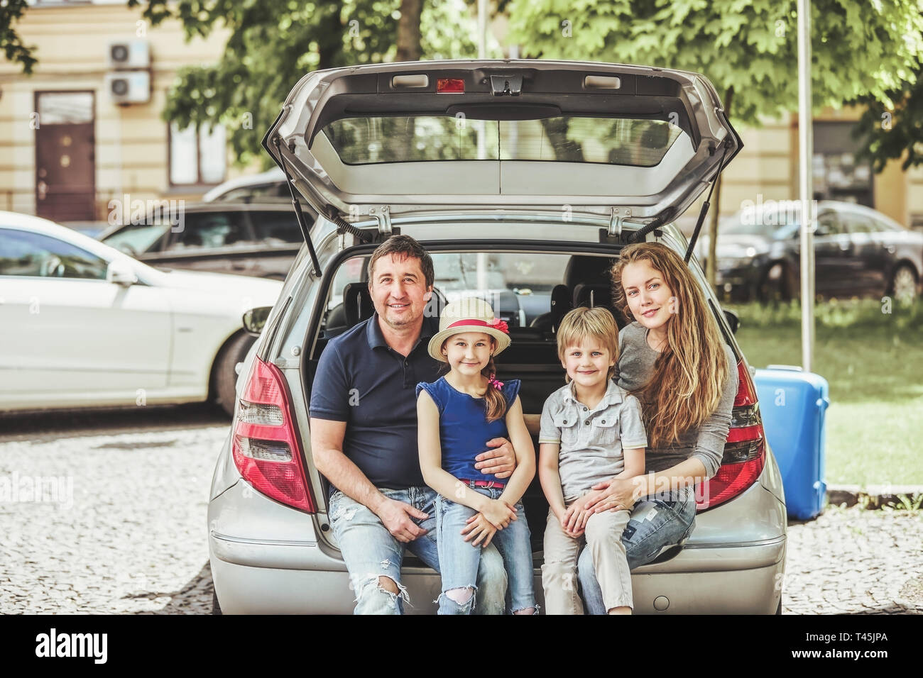 happy family sitting in the trunk of a family car . the concept of family travel - Stock Image