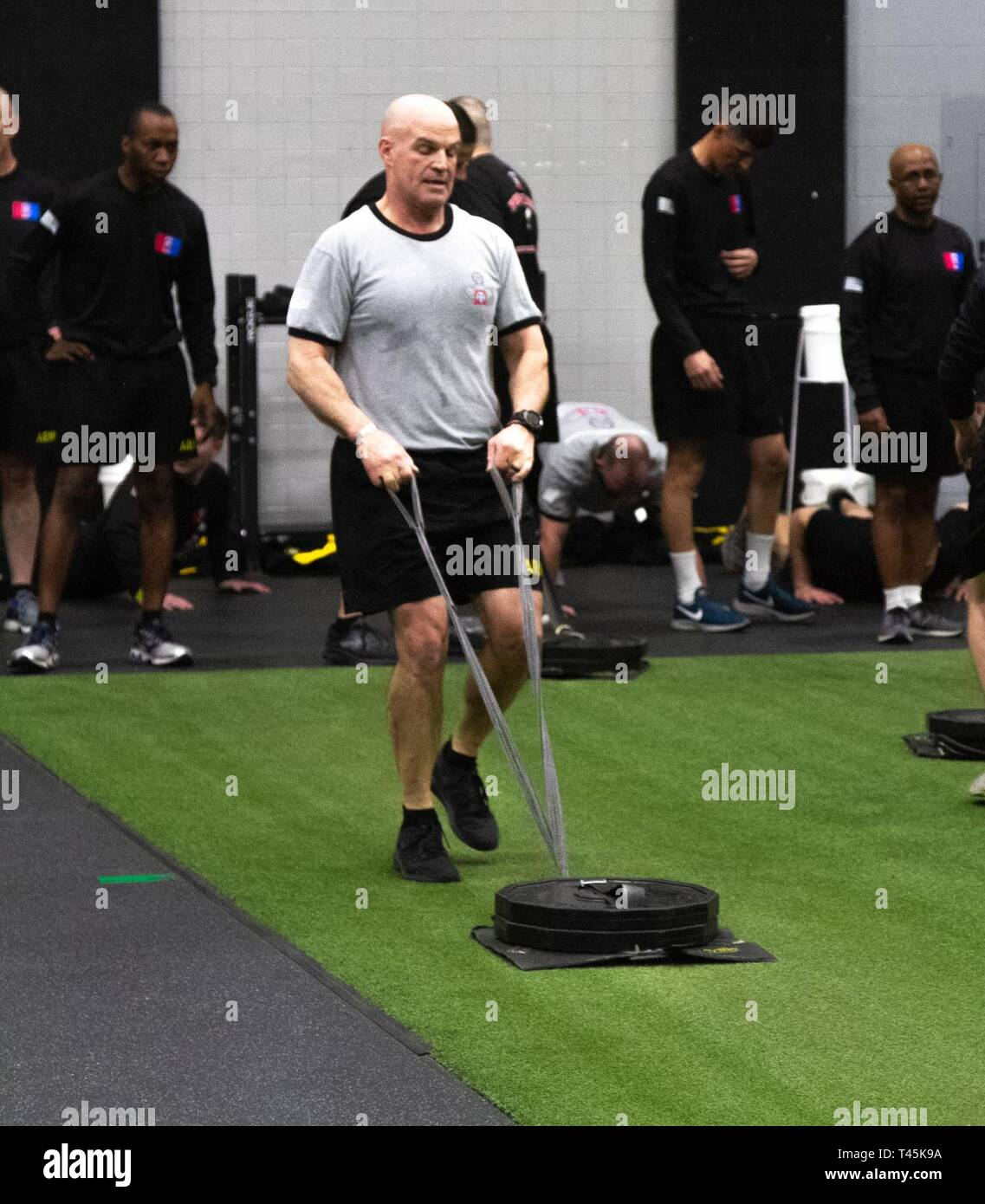 The 82nd Airborne Division Commanding General, Maj. Gen. James Mingus, completes the shuttle lane event during physical training, by pulling a weighted sled with some of the 82nd Airborne Division Sustainment Brigade Paratroopers at Tucker's gym, Fort Bragg, N.C., Mar. 1, 2019. - Stock Image