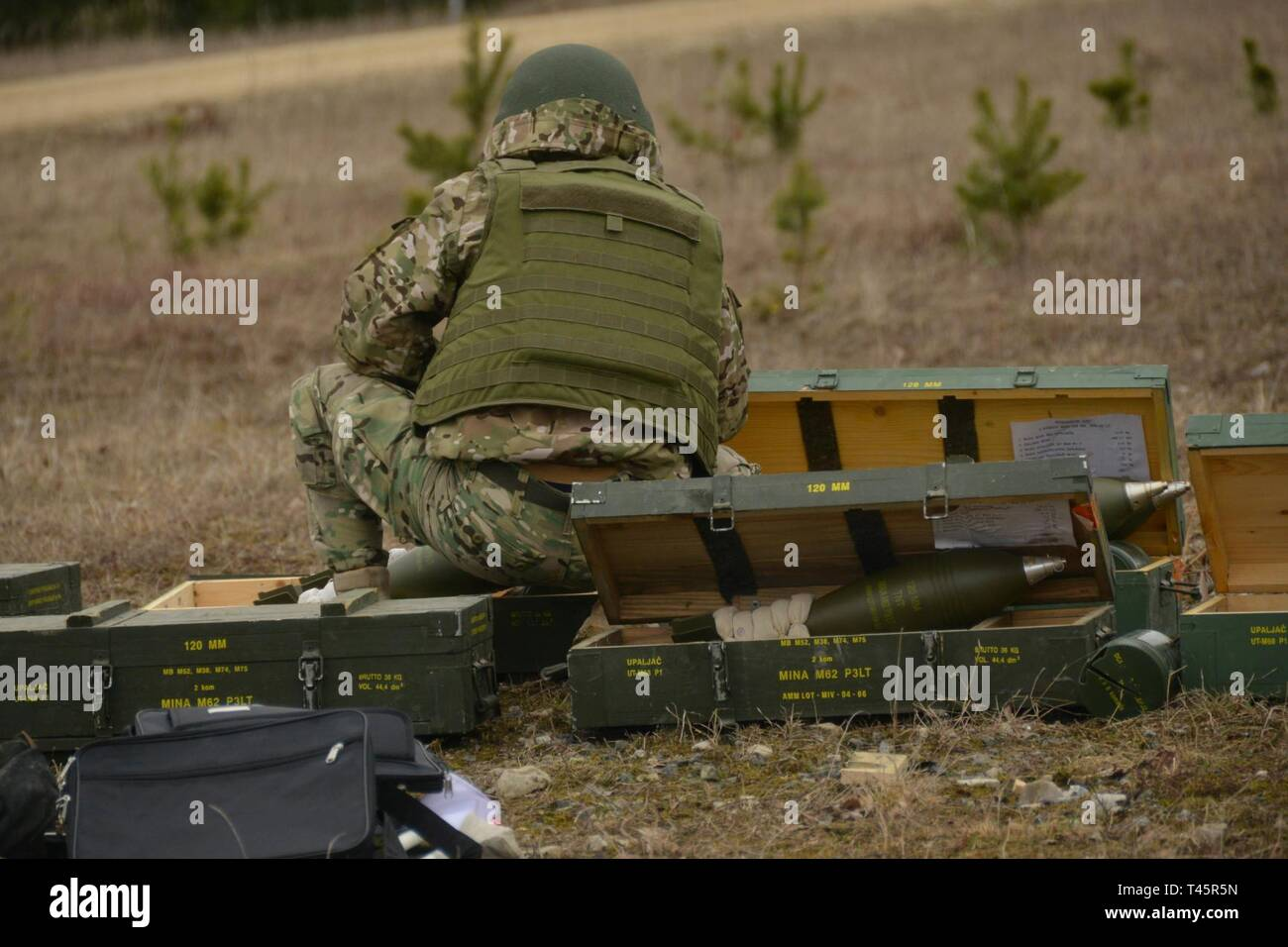 A Georgian soldier kneels in front of 120mm mortar rounds as