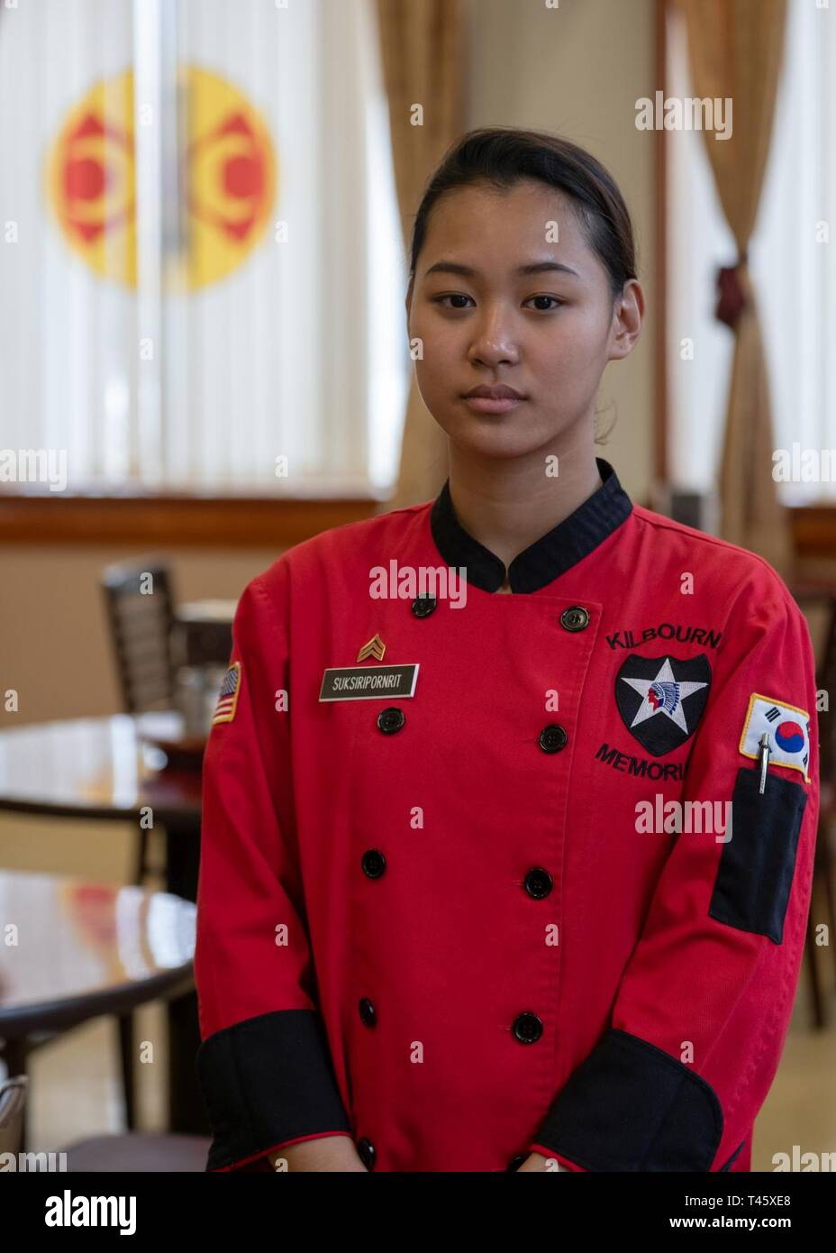 Sgt. Chanidapa Suksiripornrit, culinary specialist assigned to 61st Support Maintenance Company, 194th Combat Sustainment Support Battalion, 2nd Sustainment Brigade, an Alexandria, Va. native (originally from Bangkok, Thailand), stands proudly for a photograph inside the 210th Field Artillery Brigade (FAB) Thunder Inn dining facility (DFAC), Camp Casey, March 10, 2019. Suksiripornrit lived with her aunt and uncle in Alexandria, Va., before enlisting in 2015, and her parents remain in Bangkok, Thailand. She became an American citizen shortly after completing her Advanced Individual Training, Ju - Stock Image