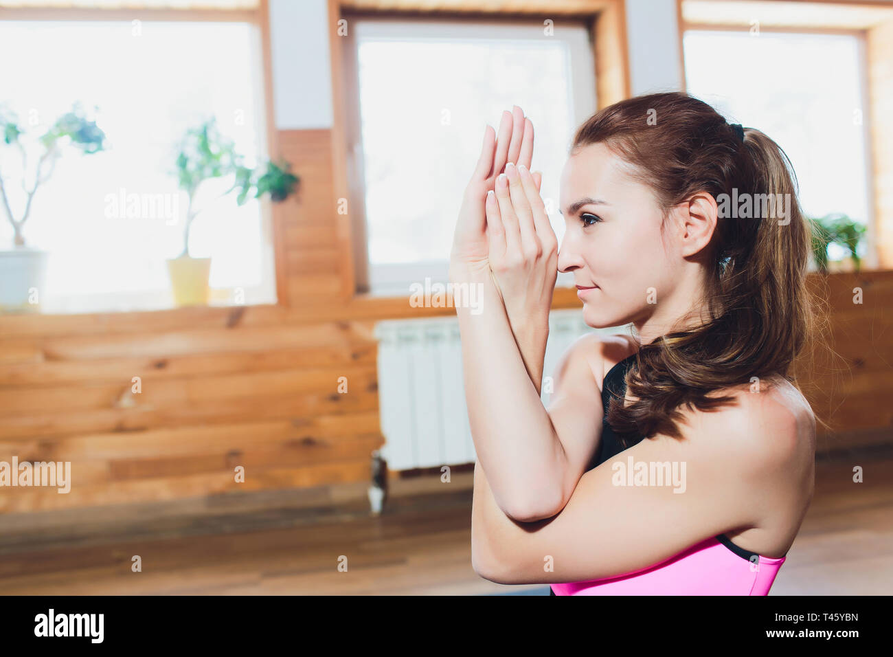 Young sporty attractive woman practicing yoga, doing Garudasana arms exercise, Eagle pose, working out, wearing sportswear,yoga studio. - Stock Image