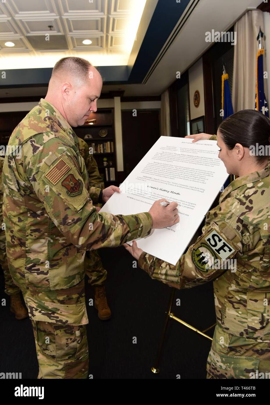 """Brig. Gen. John J. Nichols, the 509th Bomb Wing commander, signs the Women's History Month proclamation held by Master Sgt. Melissa Villalobos, the flight chief for Bravo Flight, 509th Security Forces Squadron on March 4, 2019 at Whiteman Air Force Base, Missouri. The theme of Women's History Month for 2019 is """"Visionary Women: Champions of Peace and Nonviolence."""" - Stock Image"""