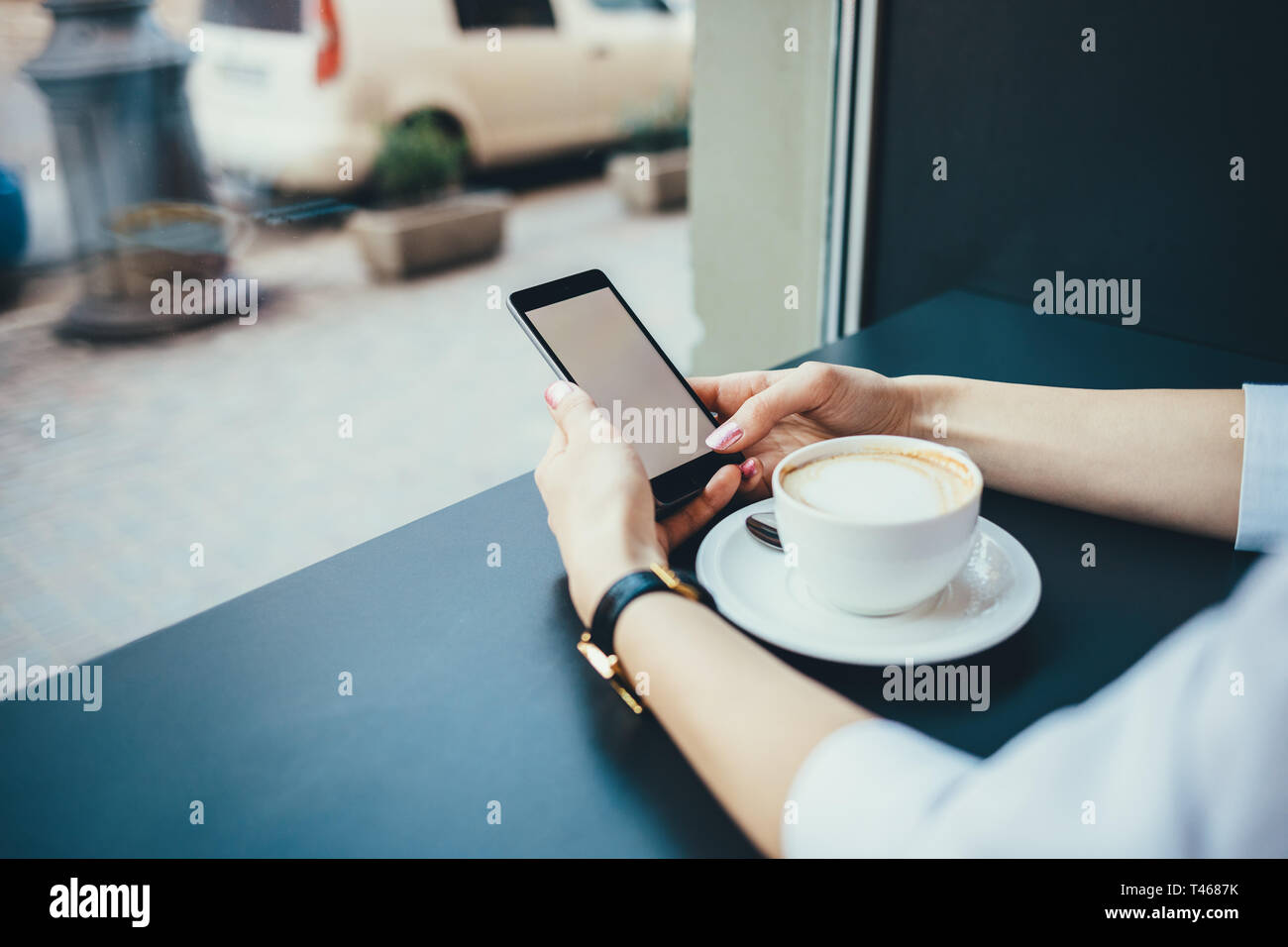 Close-up of female's hands wearing gold wristwatches holding mobile phone with empty white screen next to cup of cappuccino at table in city cafe by w - Stock Image