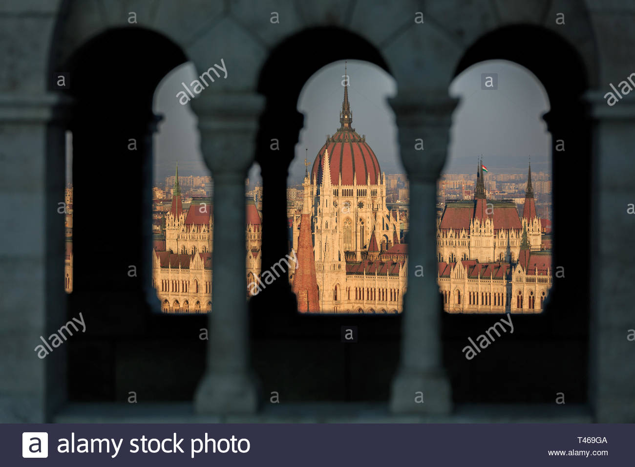The Sun Sets Across the Hungarian Parliament Building Seen Through the Struts of Fisherman`s Bastion Stock Photo