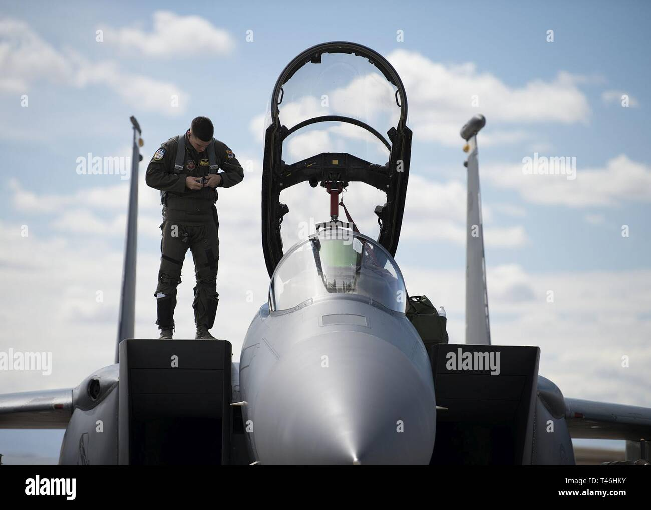 U.S. Air Force 1st Lt. Mathew Clutts, a Weapons System Officer (WSO) on an F-15E Strike Eagle fighter jet assigned to the 336th Fighter squadron, buckles up his harness while standing on top of an F-15E at Nellis Air Force Base, Nev., March 12, 2019. A WSO's job is to select targets and navigate with the aid of a moving map display, produced by an AlliedSignal remote film strip reader. Stock Photo