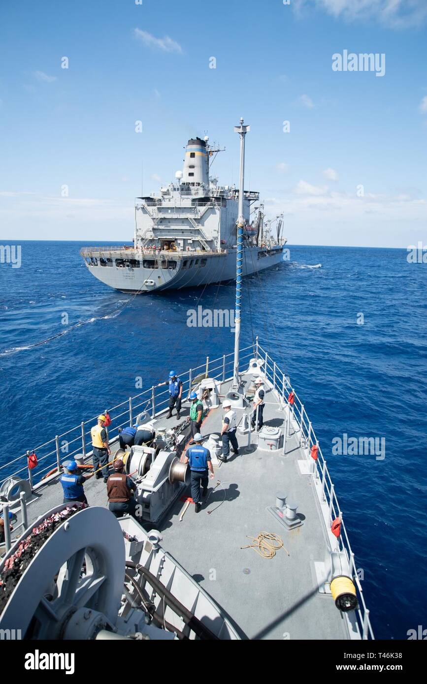 SOUTH CHINA SEA (March 16, 2019) The Avenger class mine countermeasures ship USS Chief (MCM 14) conducts a replenishment-at-sea with USNS Guadalupe (T-AO 200). Chief, part of Mine Countermeasure Squadron 7, is operating in the Indo-Pacific region to enhance interoperability with partners and serve as a ready-response platform for contingency operations. - Stock Image