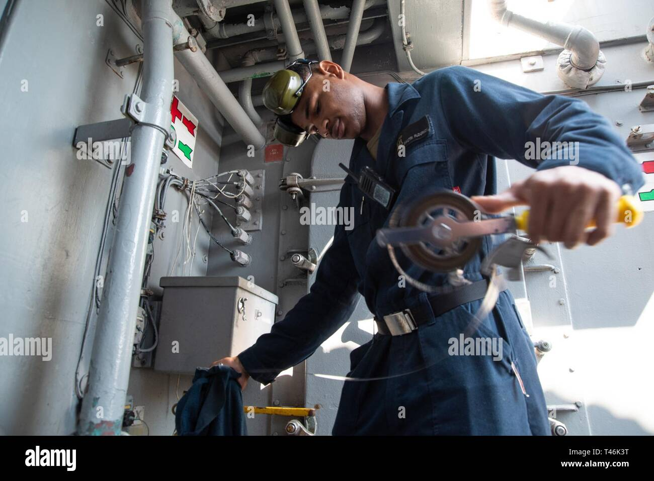 SOUTH CHINA SEA (March 16, 2019) Engineman Fireman Diautri Flournoy, from San Diego, California, measures fuel levels aboard the Avenger-class mine countermeasures ship USS Chief (MCM 14) during a replenishment-at-sea with USNS Guadalupe (T-AO 200). Chief, part of Mine Countermeasure Squadron 7, is operating in the Indo-Pacific region to enhance interoperability with partners and serve as a ready-response platform for contingency operations. - Stock Image