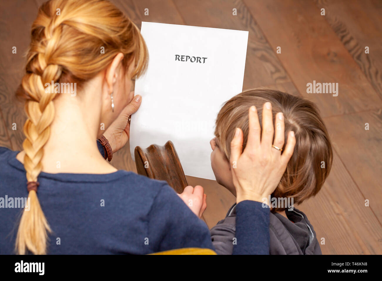 Mother comforting son despite the bad school report. - Stock Image