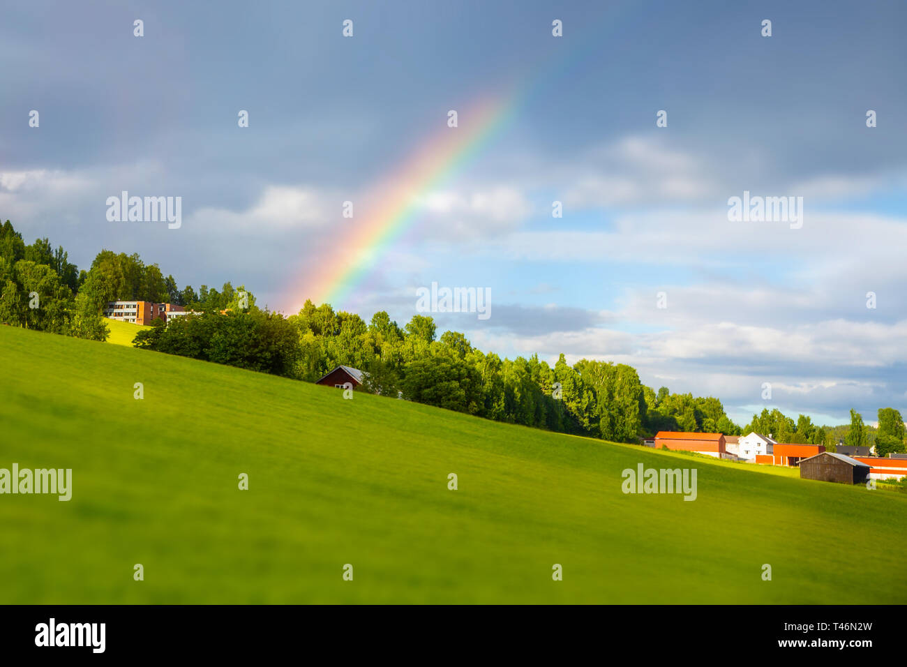 Rainbow near the house. Traditional colored wooden house in Norway at summer day. Country houses in village in Norway. - Stock Image