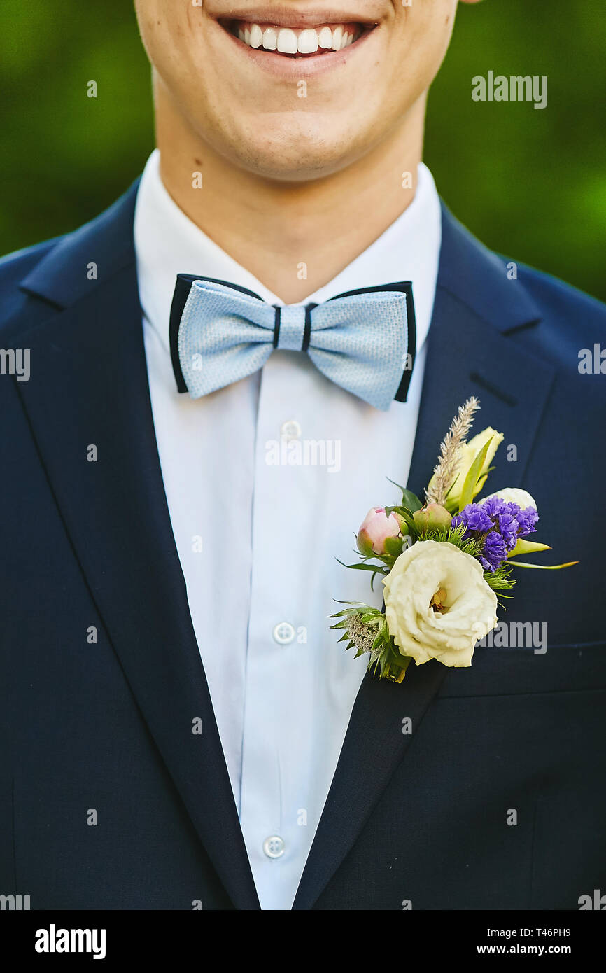 Stylish and handsome young man with the beautiful shiny smile in a blue suit with trendy bowtie and colorful boutonniere - wedding details - Stock Image