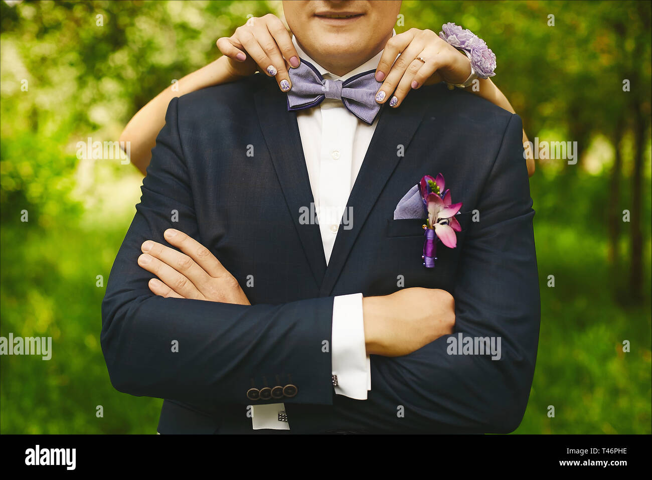 Female hands with fashionable manicure adjusting trendy bowtie on the neck of a young handsome man in a wedding suit with boutonniere - Stock Image
