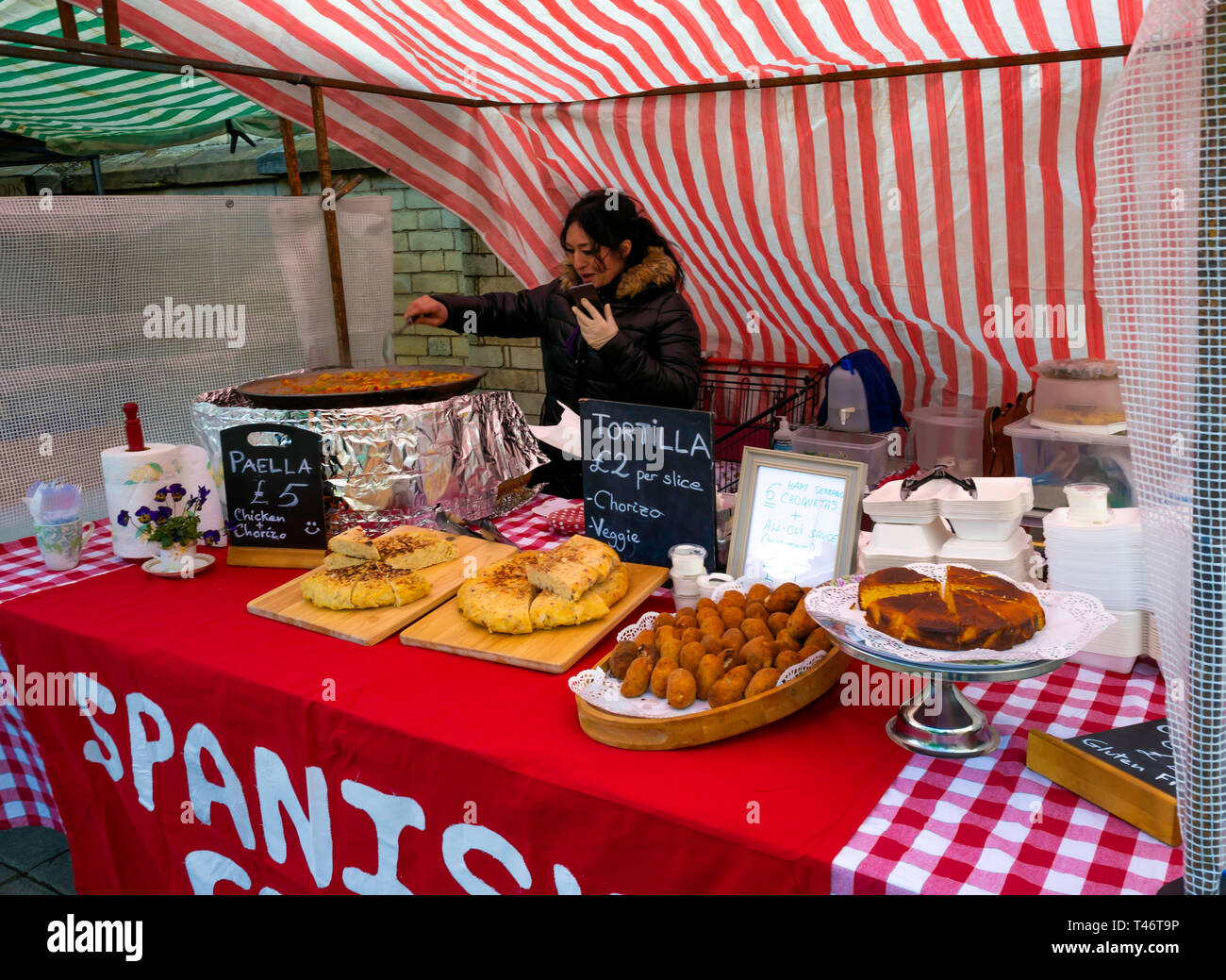 A Spanish woman stall holder at a UK farmer's market displaying food while preparing  steaming hot Paella Stock Photo