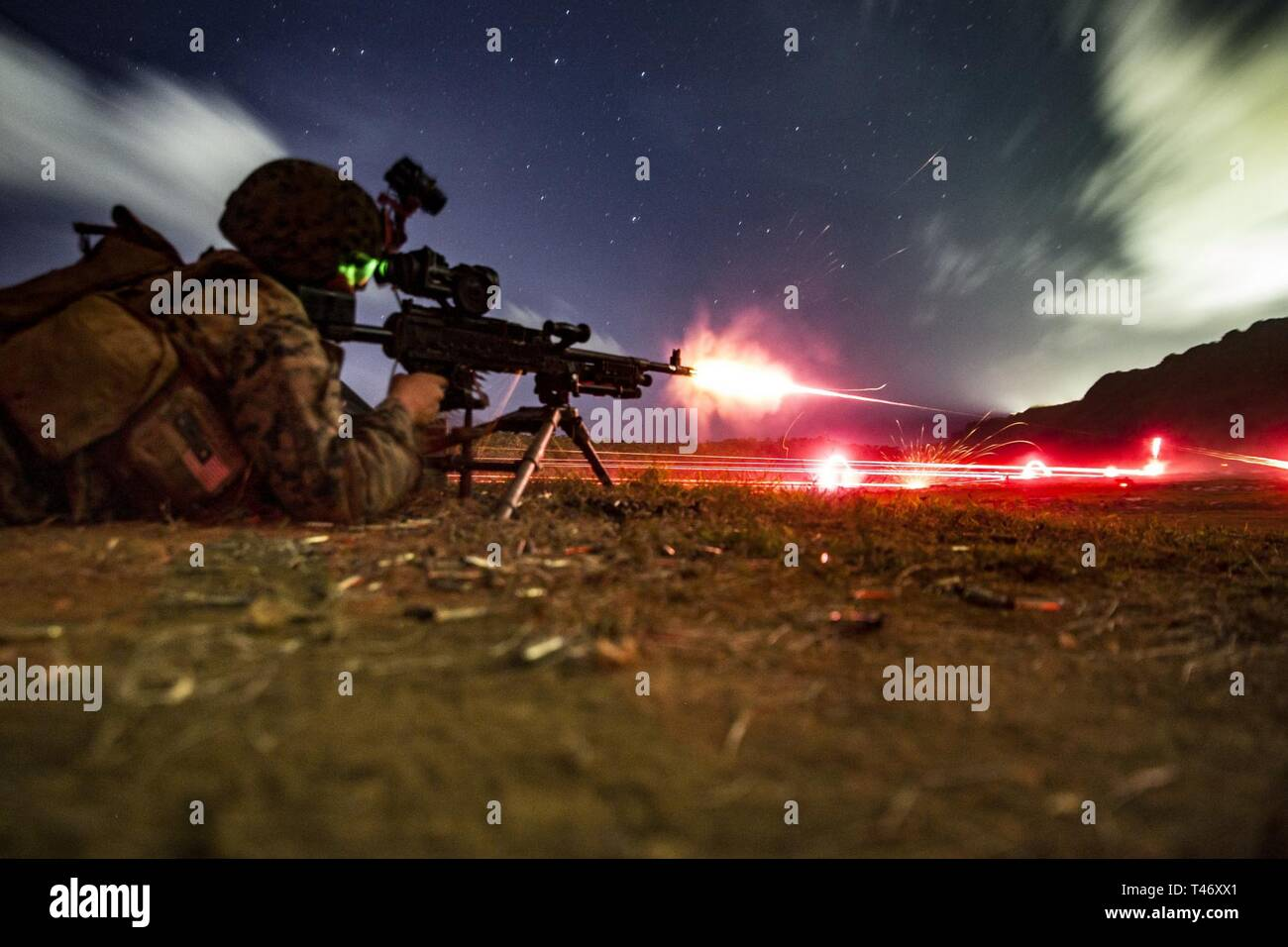 "Lance Cpl. Chris Pedroza, a rifleman with Alpha Company, Battalion Landing Team, 1st Battalion, 4th Marines, the ""China Marines,"" fires an M240G medium machine gun during low-light live-fire machine gun training at Anderson Air Force Base, Guam, March 11, 2019. Pedroza, a native of Apple Valley, California, graduated from Apple Valley High School in May 2016 before enlisting in January 2017. Alpha Company Marines are the small boat raid specialists for BLT 1/4, the Ground Combat Element for the 31st Marine Expeditionary Unit. The 31st MEU, the Marine Corps' only continuously forward-deployed M - Stock Image"