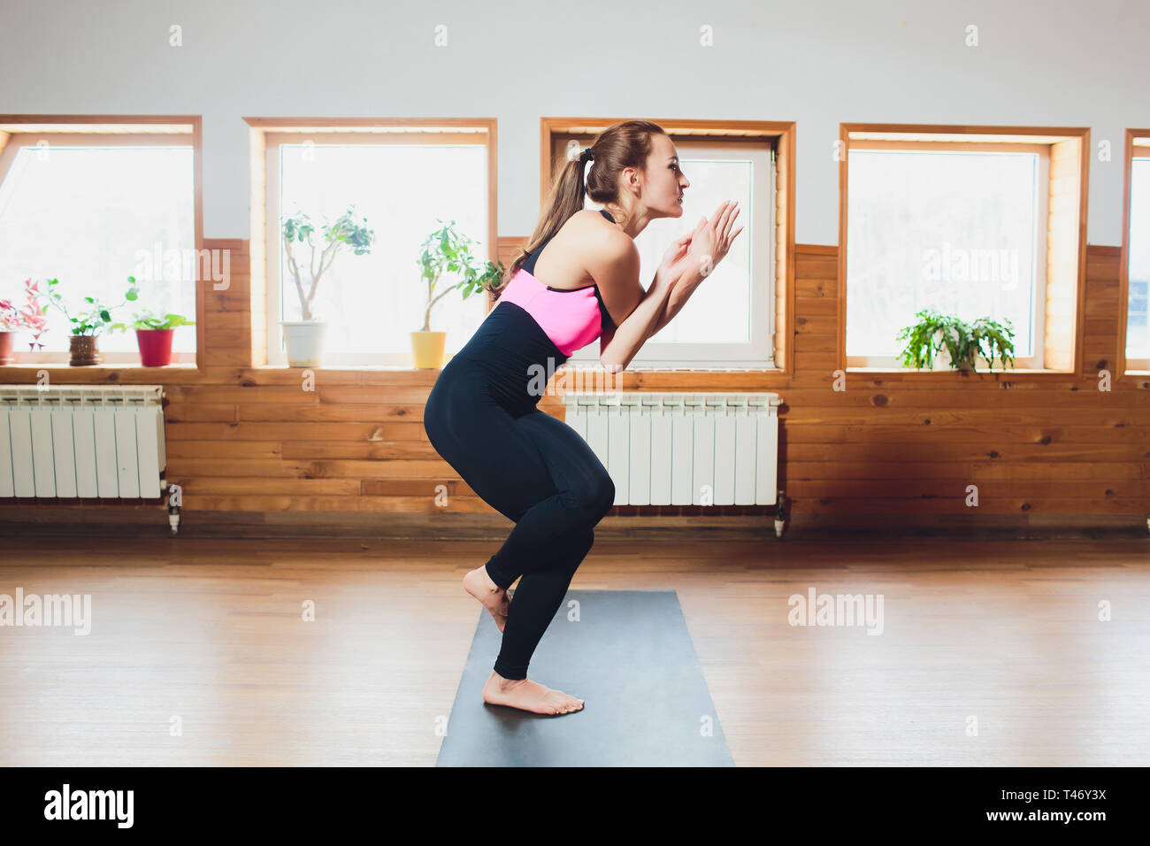 Young attractive woman practicing yoga, standing in Eagle exercise, Garudasana pose, working out, wearing sportswear, suit, indoor full length, studio - Stock Image