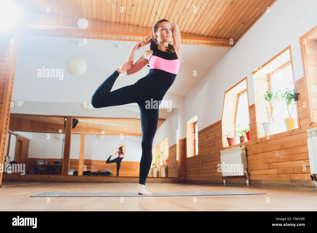 Portrait of sporty beautiful blond young woman in sportswear working out indoors, doing balance back bend, Natarajasana, Lord of the Dance posture - Stock Image