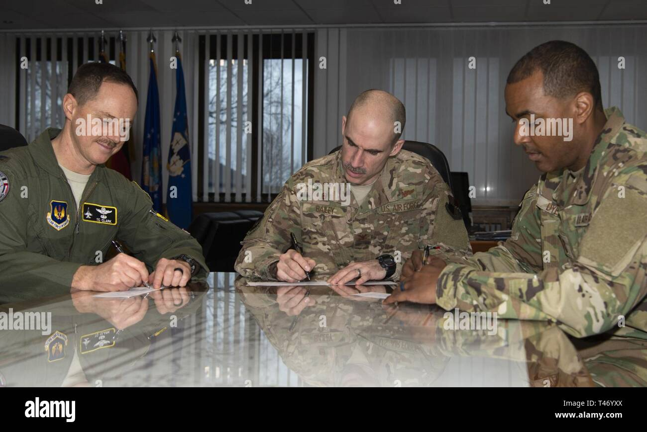 U.S. Air Force Col. Jason Bailey, 52nd Fighter Wing commander, center, Col. Tad Clark, 52nd FW vice commander, left, and Chief Master Sgt. Alvin Dyer, 52nd FW command chief, right, donate to the Air Force Assistance Fund at Spangdahlem Air Base, Germany, March 13, 2019. The AFAF includes four charities that provide support to Airmen and retiree's widowed spouses in need. - Stock Image