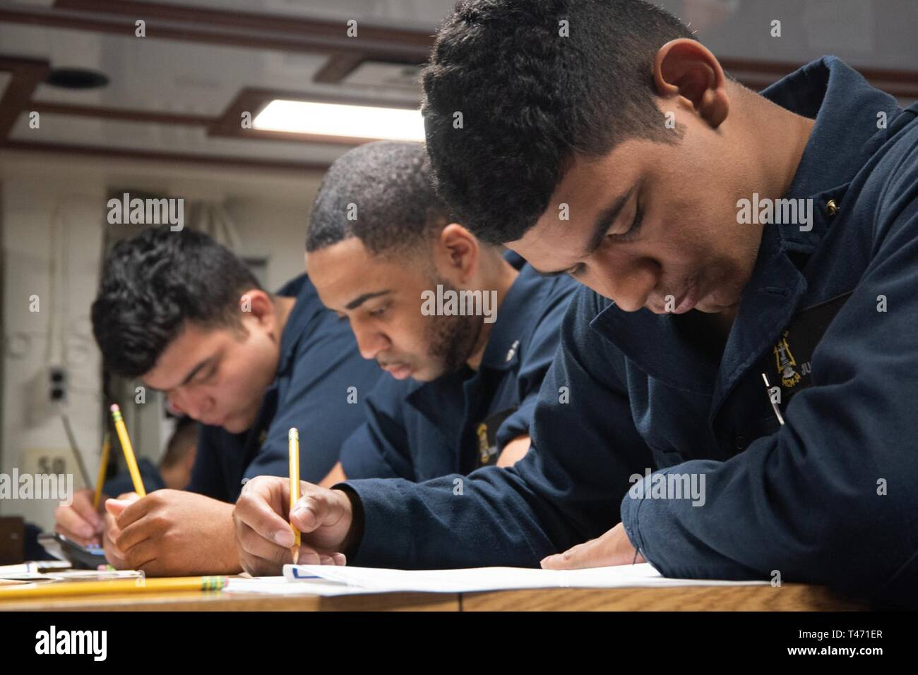 SOUTH CHINA SEA (March 14, 2019) Mineman 3rd Justin Colon (right), from Brooklyn, New York, takes the Navy-wide petty officer 2nd class advancement exam on the mess deck of the Avenger-class mine countermeasures ship USS Chief (MCM 14). Chief, part of Mine Countermeasure Squadron 7, is operating in the Indo-Pacific region to enhance interoperability with partners and serve as a ready-response platform for contingency operations. - Stock Image