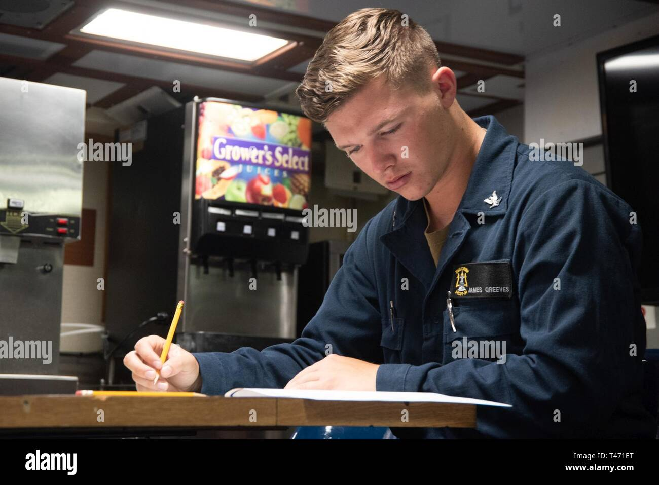 SOUTH CHINA SEA (March 14, 2019) Information Systems Technician 3rd Class James Greeves from Naples, Florida, takes the Navy-wide petty officer 2nd class advancement exam on the mess deck of the Avenger-class mine countermeasures ship USS Chief (MCM 14). Chief, part of Mine Countermeasure Squadron 7, is operating in the Indo-Pacific region to enhance interoperability with partners and serve as a ready-response platform for contingency operations. - Stock Image
