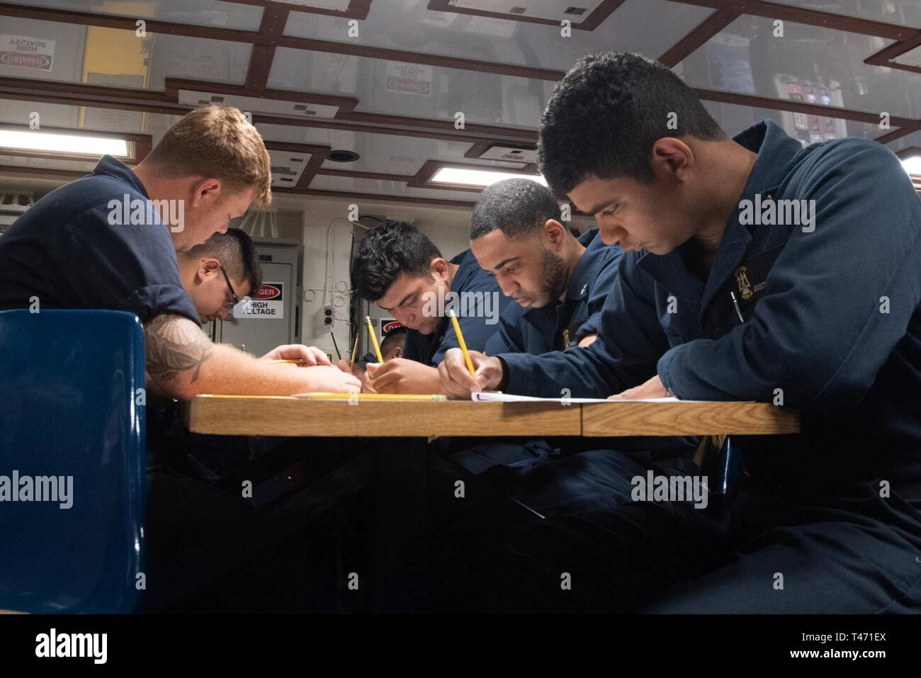 SOUTH CHINA SEA (March 14, 2019) Sailors take the Navy-wide petty officer 2nd class advancement exam on the mess deck of the Avenger-class mine countermeasures ship USS Chief (MCM 14). Chief, part of Mine Countermeasure Squadron 7, is operating in the Indo-Pacific region to enhance interoperability with partners and serve as a ready-response platform for contingency operations. - Stock Image