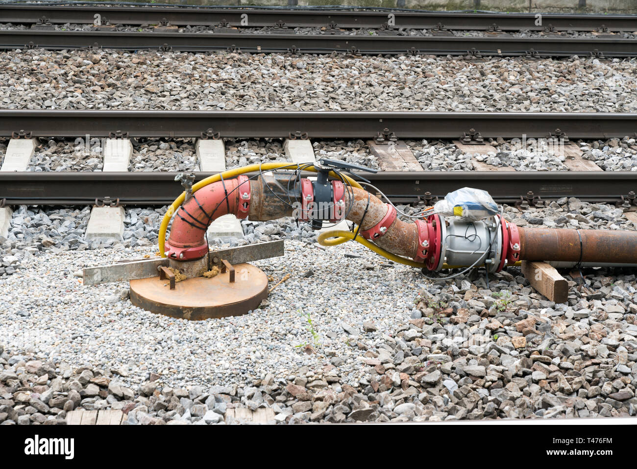 pipe and valve system with sensors and electrical wiring between railroad  tracks as a temporary supply system during construction and renovation