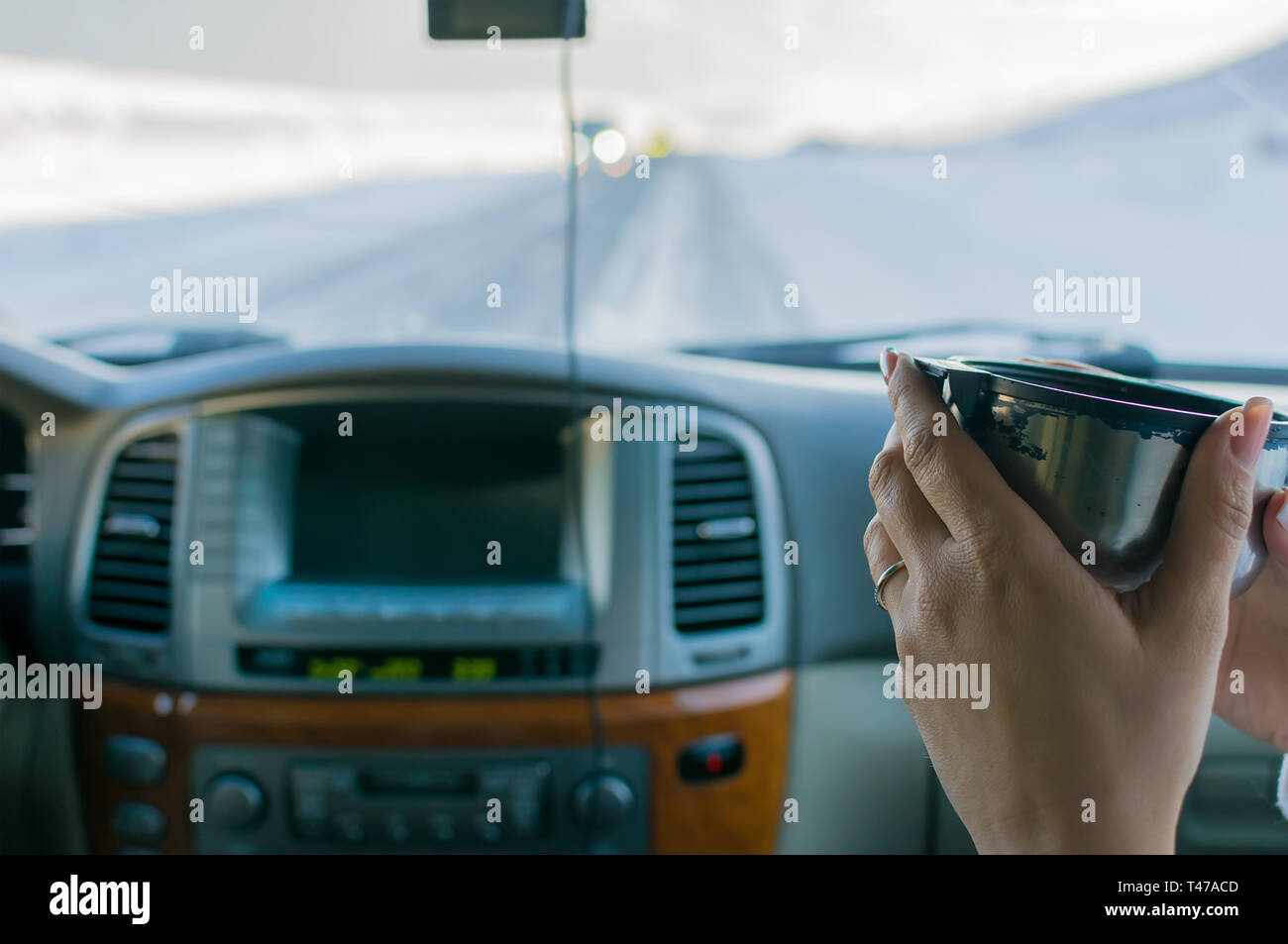 the hand of the girl in the passenger seat of the car holding hot tea from the mug from the thermos - Stock Image