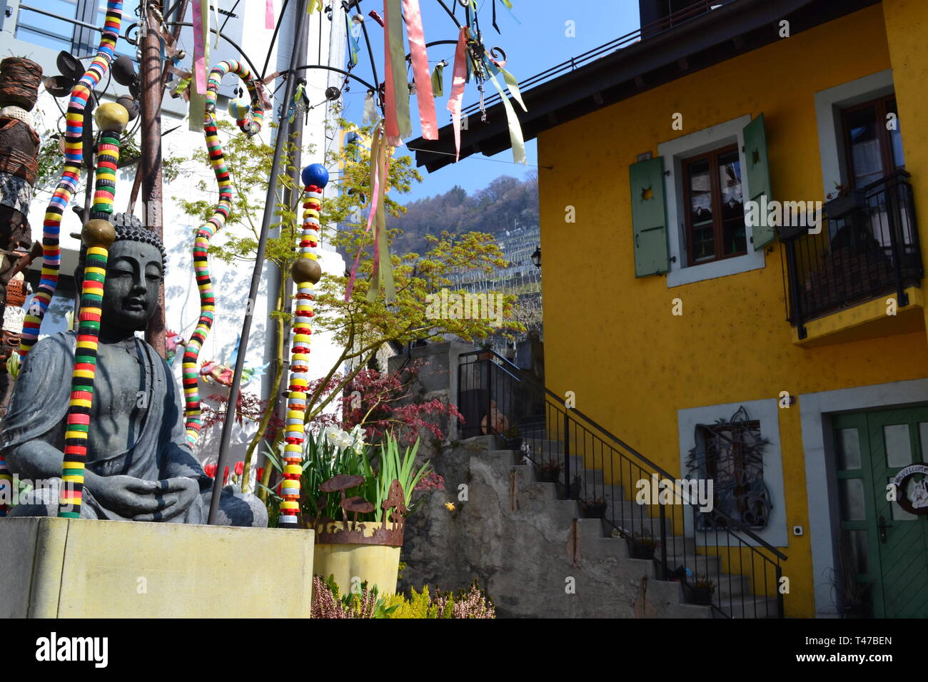 Buddha stature and imagery outside a house in Epesses village by Lake Geneva in Vaud, Lavaux, Switzerland. Opposite is a yellow house with shutters - Stock Image