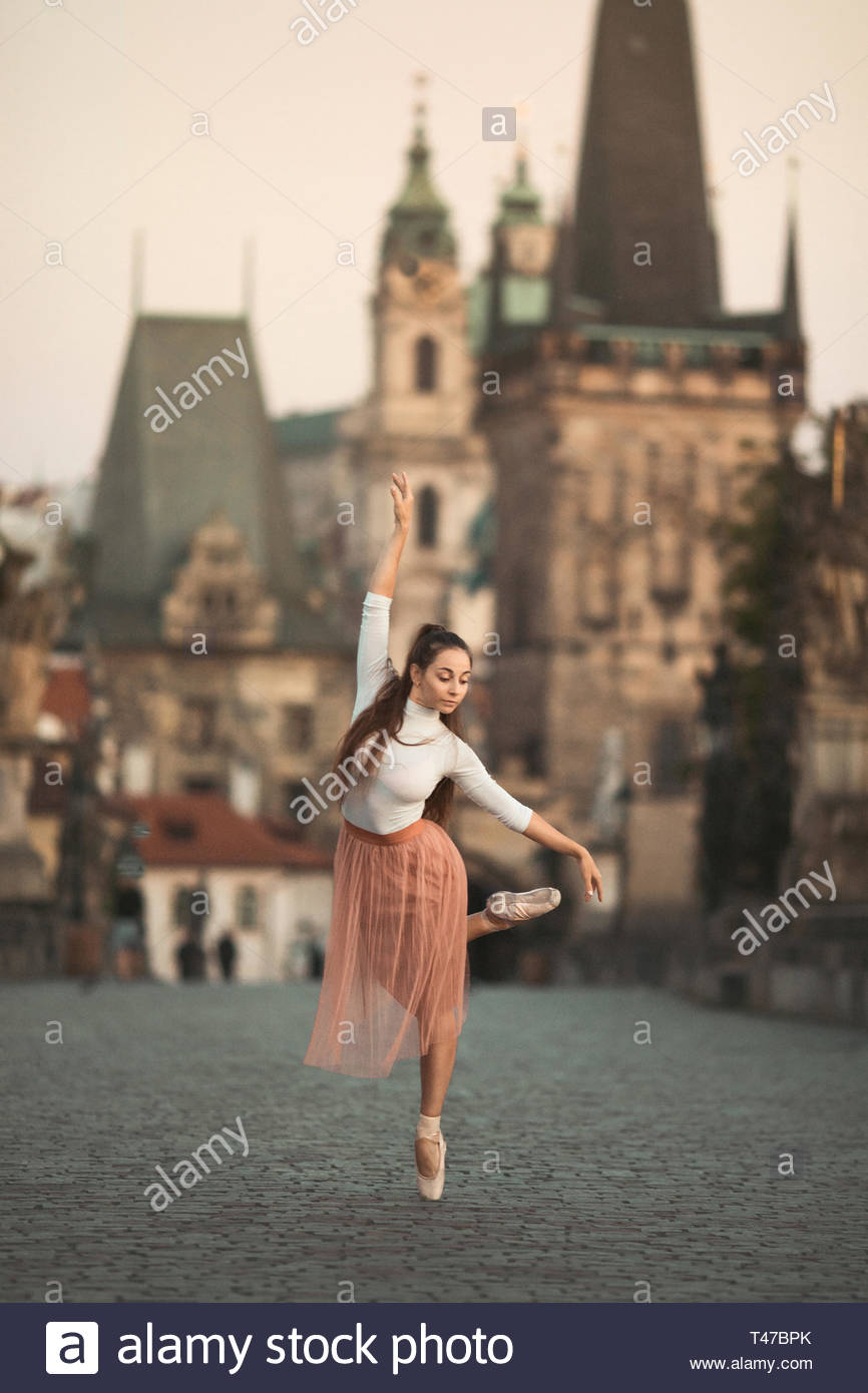 selective focus photography of ballerina tip toeing on gray concrete pavement - Stock Image