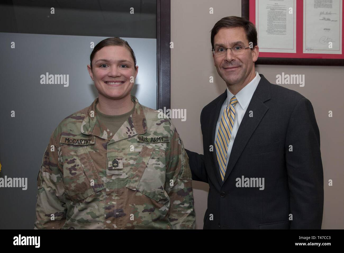 SFC Melissa McCarthy, team lead for the Massachusetts Army National Guard Joint Forces (JFHQ) Headquarters Headquarters Detachment (HHD) G1 directorate, receives a coin from Dr. Mark T. Esper, Secretary of the Army. McCarthy's team is comprised of nine soldiers who are in charge of updating 5,800 service members records.     Sec. Esper joined Maj. Gen. Gary W. Keefe, the Adjutant General of the Massachusetts National Guard and other senior leadership during a visit to Joint Force Headquarters of the Massachusetts National Guard, here, March 15, 2019. After an awards ceremony held to recognize  - Stock Image